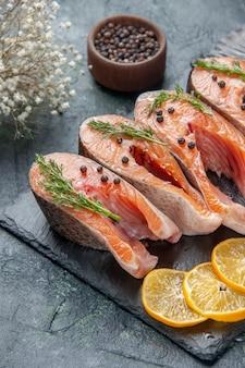 Vista frontale di freschi pesci crudi verdi pepe e fette di limone sul vassoio di colore scuro sulla tabella colori mix