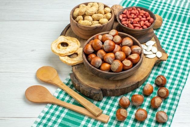 흰색 표면에 땅콩과 전면보기 신선한 원시 헤이즐넛 무료 사진