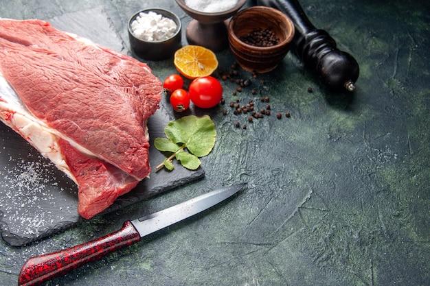 Vista frontale di carne rossa cruda fresca su vassoio nero pepe sale limone coltello a martello in legno su sfondo di colore scuro