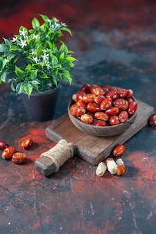 Front view of fresh raw silverberry fruits in a bowl on a wooden cutting board and flower pot on mix colors background