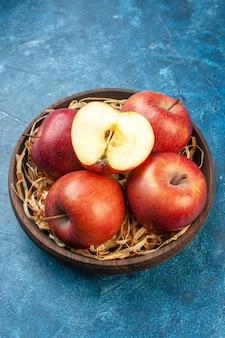 Vista frontale mele rosse fresche all'interno del piatto sulla superficie blu