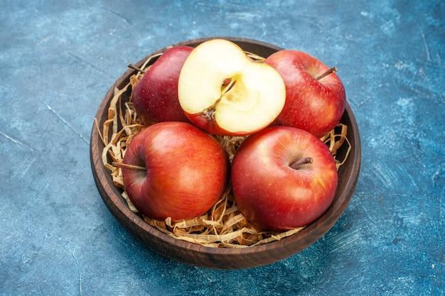 青い表面のプレートの内側の正面図新鮮な赤いリンゴ