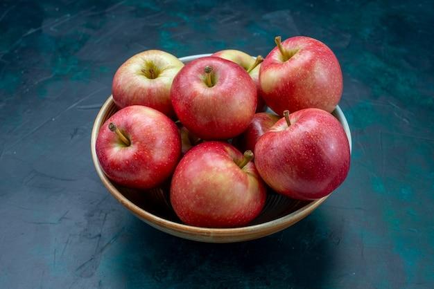 Вид спереди свежие красные яблоки сочные и мягкие внутри тарелки на темно-синем столе фрукты свежий мягкий витамин