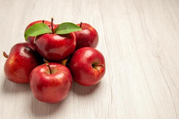 正面図新鮮な赤いリンゴは、明るい白い机の上のまろやかで熟した果物果物の色新鮮な植物の赤い木