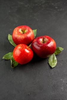 Вид спереди свежие красные яблоки, спелые фрукты на темном столе, фрукты, красные свежие спелые деревья