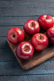 Vista frontale mele rosse fresche frutti maturi dolci su scrivania blu scuro colore rosso pianta fresca vitamina