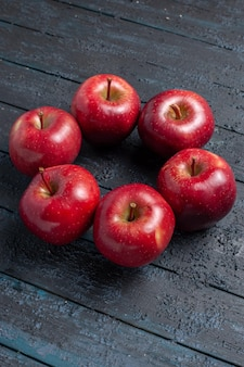 Front view fresh red apples mellow and ripe fruits on the dark-blue desk fruit whole color red plant vitamine fresh