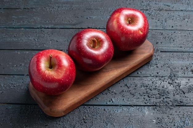 Vista frontale mele rosse fresche frutti maturi dolci su scrivania blu scuro colore rosso vitamina frutta pianta fresca