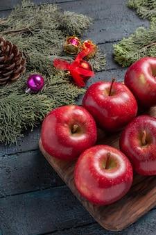Vista frontale mele rosse fresche frutti maturi dolci su piante da scrivania blu scuro molti colori di frutta vitamina rosso fresco