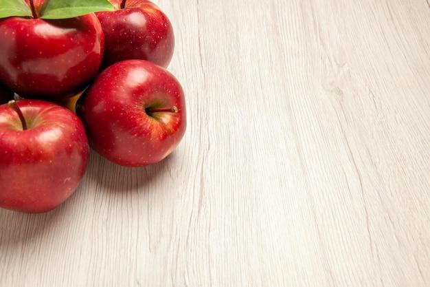 Vista frontale mele rosse fresche frutti dolci e maturi su un albero rosso di piante fresche di colore bianco chiaro della scrivania