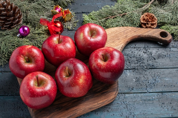 正面図新鮮な赤いリンゴは紺色の机の上に熟した果実をまろやかにし、多くの果実の色を新鮮なビタミンレッドに植えます