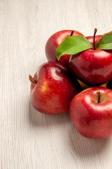 Vista frontale mele rosse fresche frutti dolci e maturi su scrivania bianca frutti colorano pianta fresca albero rosso