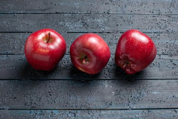 Вид спереди свежие красные яблоки, спелые и спелые фрукты на темно-синем столе, много фруктовых деревьев красного цвета свежего растения