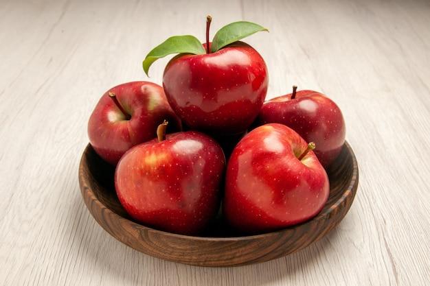 Vista frontale mele rosse fresche frutti maturi e morbidi sulla scrivania bianca albero colore frutta pianta fresca rossa