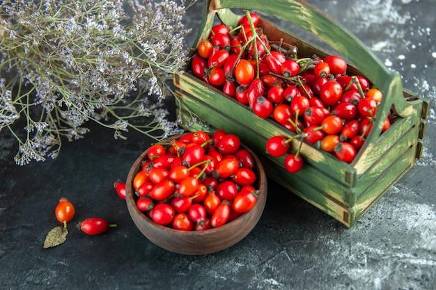 Bacche rosse fresche di vista frontale su una foto di frutta di colore selvaggio della bacca di salute della scrivania di legno scuro