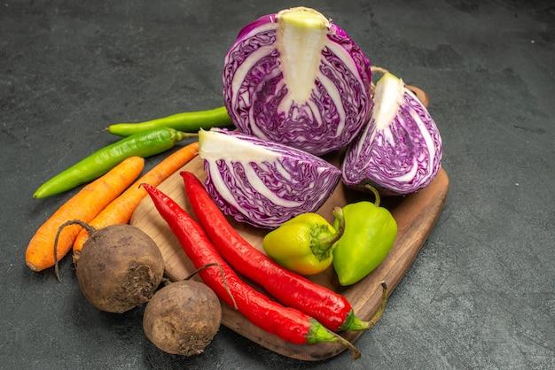 Cavolo rosso fresco di vista frontale con altre verdure sulla salute matura dell'insalata di dieta della tavola scura