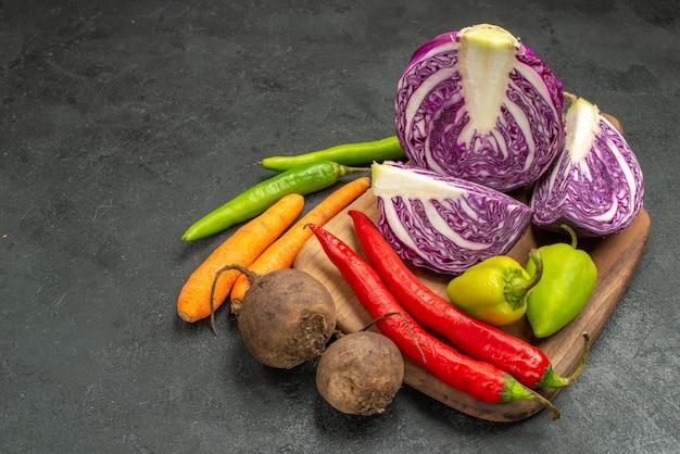 Вид спереди свежей красной капусты с другими овощами на темном столе, диетическом спелом салате