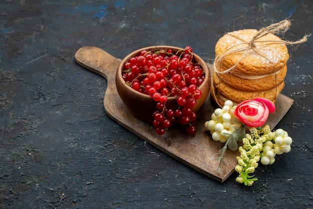 Вид спереди свежей красной клюквы внутри миски с сэндвич-печеньем с кремовой начинкой на темной поверхности, сладкий сахар
