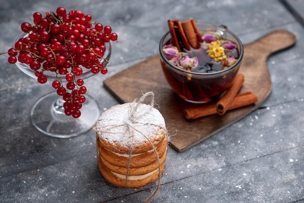 正面の新鮮な赤いクランベリーと紅茶のサンドイッチクッキーとシナモングレーデスクフルーツベリーの新鮮なお茶