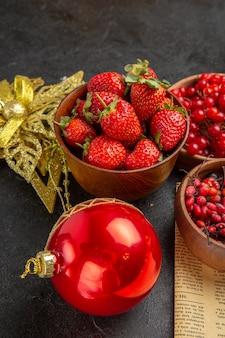 暗い背景の上のクリスマスのおもちゃの周りの他の果物と新鮮な赤いクランベリーの正面図フルーツ色クリスマスホリデーベリー
