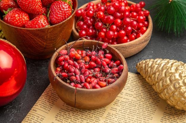 暗い背景色のクリスマスのおもちゃの周りの他の果物と新鮮な赤いクランベリーの正面図クリスマスホリデーフルーツベリー