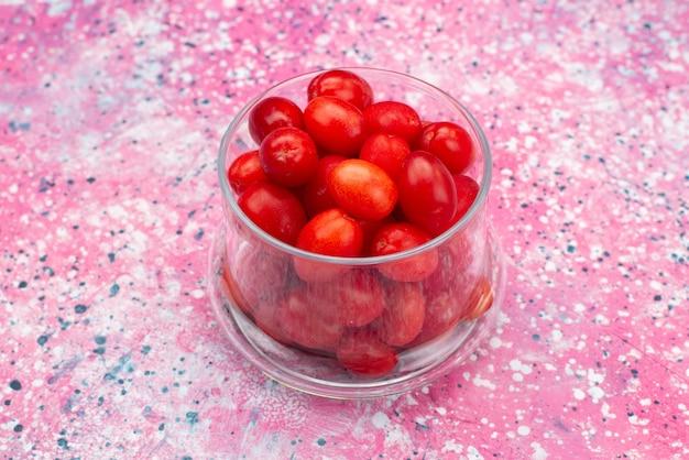 Вид спереди свежие красные фрукты, спелые, кислые и спелые внутри прозрачного стекла на ярком столе, фруктово-ягодные свежие