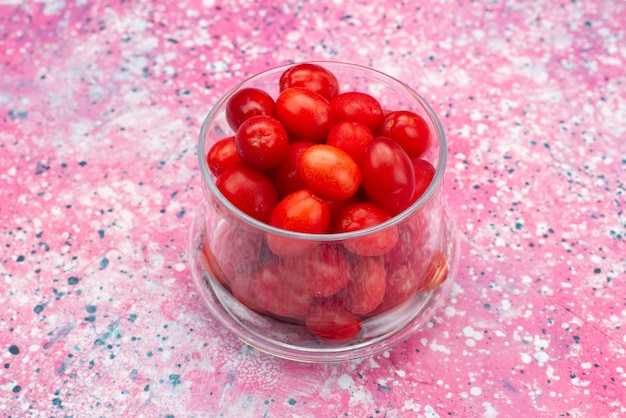 Front view fresh red fruits mellow sour and ripe inside transparent glass on the bright desk fruit berry fresh
