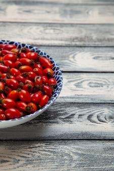 正面図灰色の表面のフルーツベリー色のビタミンの木のプレート内の新鮮な赤い果実熟した酸っぱい果実