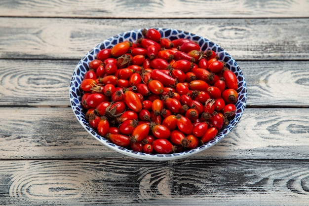 正面図灰色の表面のプレート内の新鮮な赤い果実熟した酸っぱい果実果実の果実色のビタミンの木の植物