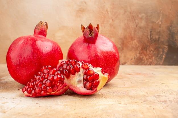 正面図明るい背景の新鮮な赤いザクロ赤い色の写真まろやかな果物