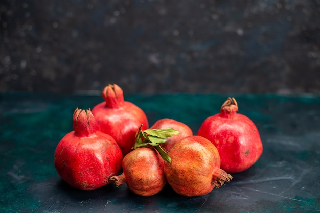 Front view of fresh red pomegranates on dark surface