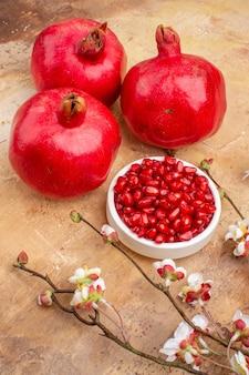 Vista frontale di melograni rossi freschi sbucciati e con frutti interi su sfondo marrone colore di frutta foto succo morbido