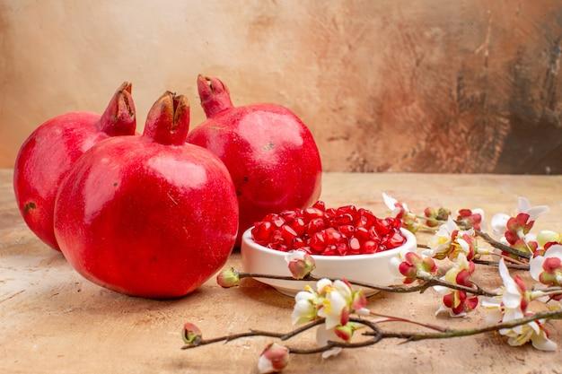 Vista frontale dei melograni rossi freschi sbucciati e con frutti interi su sfondo marrone foto di frutta a colori