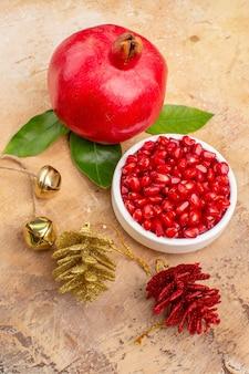 Vista frontale di melograni rossi freschi sbucciati e con frutti interi su sfondo chiaro succo di frutta foto dolce