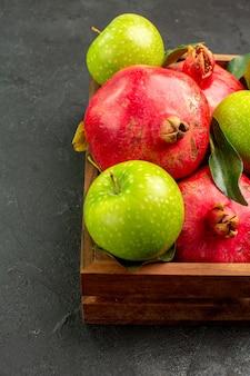 Melograni rossi freschi di vista frontale con le mele verdi sul colore della frutta matura di superficie scura