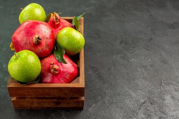 어두운 책상 익은 과일 색상에 녹색 사과와 전면보기 신선한 붉은 석류