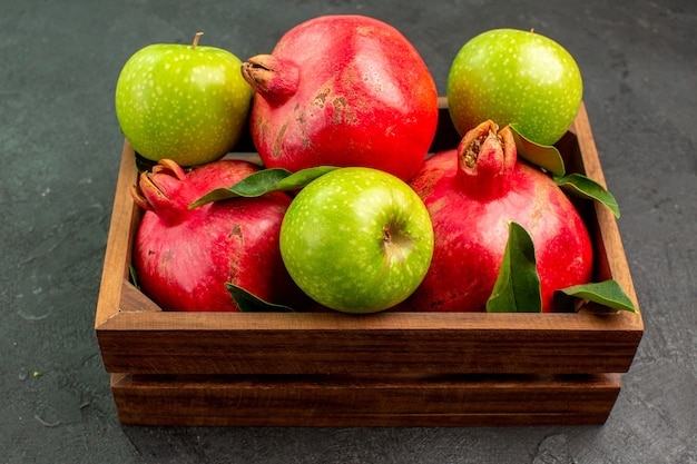 어두운 표면 익은 과일 색상에 녹색 사과와 전면보기 신선한 빨간 석류