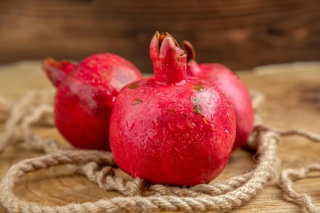 Melagrane rosse fresche di vista frontale con le corde sull'albero della foto del succo di frutta di colore della scrivania in legno wooden