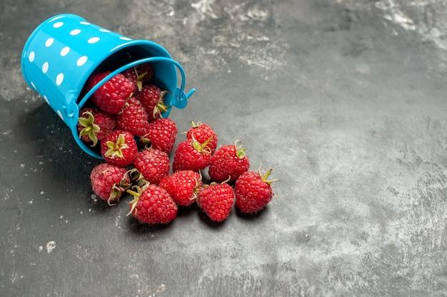 グレーのフルーツ カラー クランベリーの写真のベリーの小さなバスケットの中の正面新鮮な赤いラズベリー