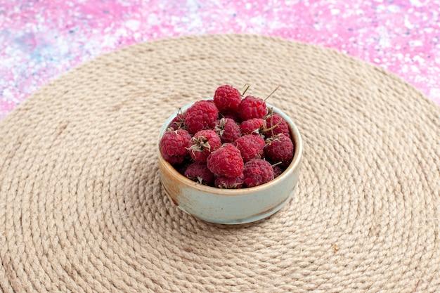 ピンクの背景の小さな鍋の中の新鮮な赤いラズベリーの正面図。