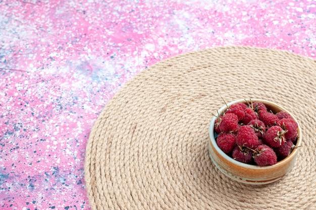 Вид спереди свежие красные малины внутри горшка на розовом фоне.