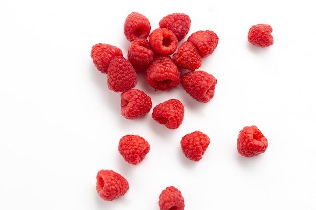 Вид спереди свежей красной малины, спелой и кислой на белом