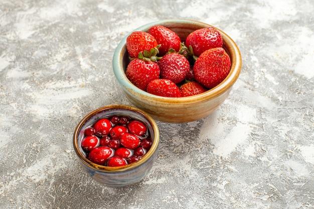 Fragole rosse fresche di vista frontale all'interno della piccola pentola sulla bacca rossa della frutta di superficie bianca