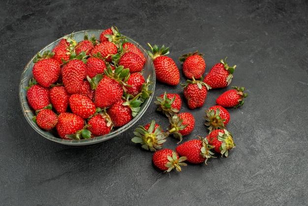 Вид спереди свежей красной клубники внутри тарелки и на сером фоне ягодного дерева сока цвета лета