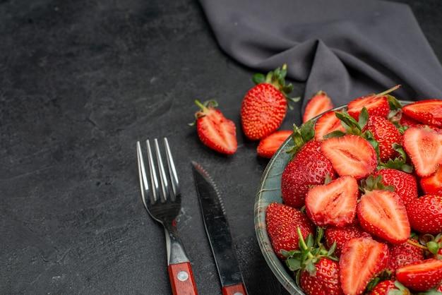 Вид спереди свежей красной клубники внутри тарелки со столовыми приборами на темном фоне цветных лесных ягод летнего сока дерева