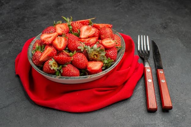 Вид спереди свежей красной клубники внутри тарелки со столовыми приборами на темном фоне летнего цветного древесного сока ягоды дикой природы