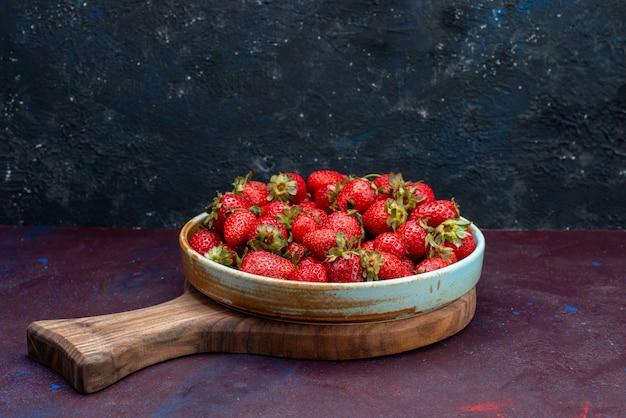 Vista frontale fresche fragole rosse mellow frutti bacche sullo sfondo blu scuro frutti di bosco mellow summer food vitamin mature