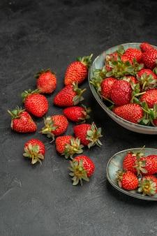 Вид спереди свежей красной клубники на сером фоне летнего цвета ягоды сока дикого дерева