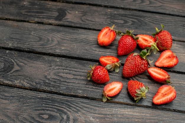 Вид спереди свежей красной клубники, нарезанной и целых фруктов на темном деревянном деревенском столе, летний цвет, сок дикого дерева, ягода