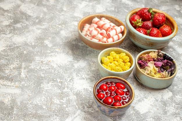 Вид спереди свежей красной клубники с конфетами на светлой поверхности фруктово-ягодной сладости